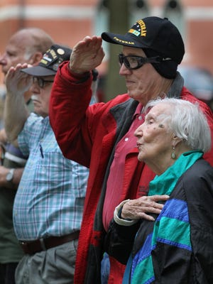 From left, veterans LaVerne Neve and Wayne Pittsley, both of Marshfield, salute during the playing of the National Anthem as Pittsley's mother Bea Pittsley, also of Marshfeild sings at the Marshfield Civic Band's opening concert of the summer at Columbia Park, Wednesday, June 17, 2015.