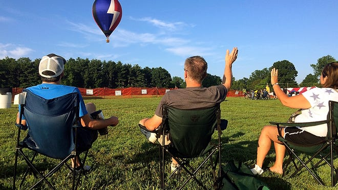 Spectators wave to pilot Jim Cusik in balloon Bolt as he flies over Freer Field during last year's BalloonFest. No mass gathering is planned this weekend due to the COVID-19 pandemic. Instead, balloons will launch from various locations and folks will be able to participate in activities via Facebook.