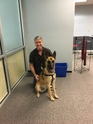 Dash the Belgian Malinois poses with his human Steve