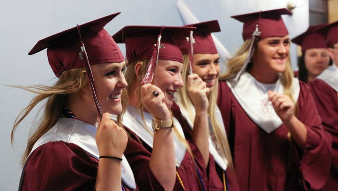 Allison Haycraft, 17, far left, practiced turning her tassel with a group of classmates just before the graduation ceremony for the Holy Cross High School at the Memorial Auditorium. 