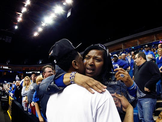 Memphis' Chris Crawford kisses his mother, Betty Crawford, while holding the 2013 C-USA tournament MVP trophy.