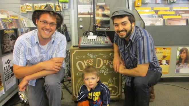 Joe Mailander, left, and Justin Lansing are the Okee Dokee Brothers (here with a new friend).