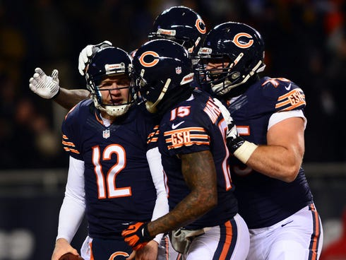 Chicago Bears quarterback Josh McCown (12) celebrates with teammates after rushing for a touchdown during the second quarter against the Dallas Cowboys at Soldier Field.
