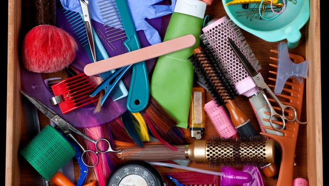 Junk drawer with hair related objects.