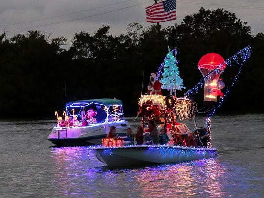 Participants in the Capri Christmas Boat Parade wave as they pass by.