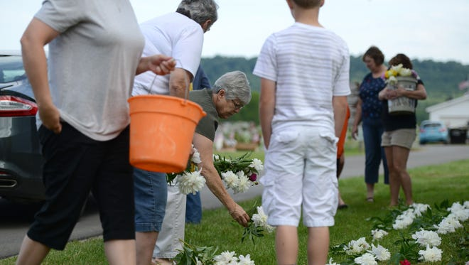 Women lay fresh cut flowers outside the church for visitors to place on the graves of veterans after the parade. Visitors gathered in front of the Londonderry Friends Church on Monday for the annual Memorial Day Parade.
