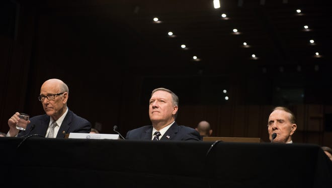 Mike Pompeo, nominee for CIA Director, center, sits with Senator Bob Dole, right, during confirmation hearing before the Senate Select Committee on Intelligence.