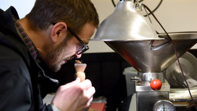 Corey Gerlach smells the coffee while roasting beans at the Breaks Coffee Roasting Co. in Sioux Falls on Thursday.