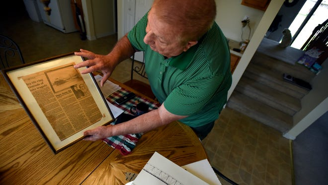 Russ Humphrey shows a newspaper clipping of a story about the life ring he found in 1958 from the S.S. Carl D. Bradley Friday, April 14, at his home in Chesterfield Township.