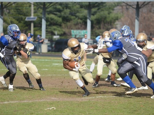 Hackensack's Justin Vick (No. 11) tries to avoid a tackle from Teaneck at the annual Thanksgiving game in 2015.