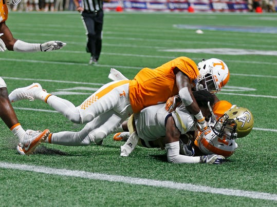 Georgia Tech running back Qua Searcy (1) loses his helmet as he is stopped short of the goal line by Tennessee defensive back Rashaan Gaulden (7) in the second half of an NCAA college football game, Monday, Sept. 4, 2017, in Atlanta. (AP Photo/John Bazemore)