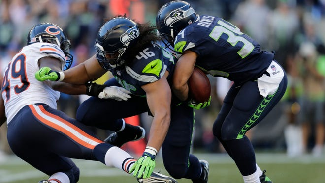 Seattle Seahawks running back Thomas Rawls, right, rushes as Will Tukuafu (46) blocks Chicago Bears' Sam Acho, left, in the second half of an NFL football game, Sunday, Sept. 27, 2015, in Seattle.