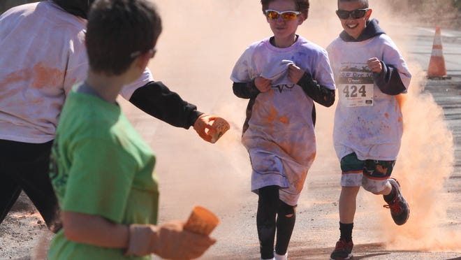 Dylan Cupen (far right), 10, gets Keri Weber along with her daughter Beth, 3, and baby Jake, 9 months, during the Do or Dye 5K. Runners were splattered with colored corn starch (left) during the American Cancer Society event.