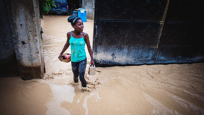 A girl walks through floodwaters that have come down from the mountains outside Port-au-Prince on Oct. 5, 2016.