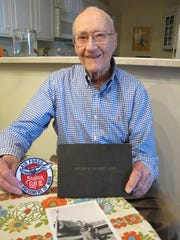 Tom Wilson holds his pilot's log book from WWII and a Stalag Luft III Prisoner of War survivors patch in his Mequon home. Tom Wilson was a B-25 pilot shot down in Africa on his seventh mission in April 1943. He spent more than two years in a German POW camp. Wilson now wonders if perhaps his generation did not do a good enough job educating subsequent generations about the horrors of World War II.
