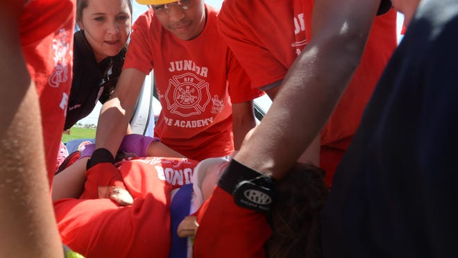 EMTs Brandi Van Meter, left, and Krisann Hittle teach camp participants how to remove a patient from an automobile.