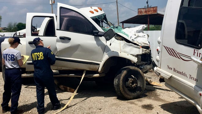 In this March 31, 2017, photo, provided by National Transportation Safety Board, Kristin Poland and David Pereira examine the pickup truck involved in a crash on March 29 on U.S. 83 near Garner State Park in Texas. Federal investigators are trying to determine whether a pickup driver's texting and drug use contributed to a head-on collision with a church bus that killed its driver and 12 passengers, according to a preliminary report released Thursday, May 4. (Jennifer Morrison/NTSB via AP)