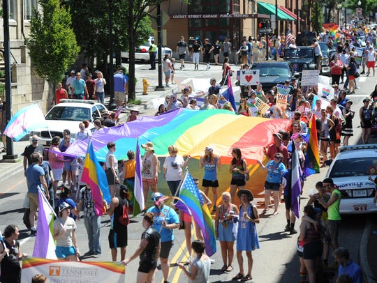 Marchers spread a gay pride flag over Clinch Ave. during