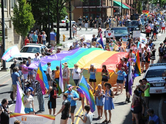 Marchers spread a gay pride flag over Clinch Avenue during the 2016 Knoxville PrideFest Parade on Saturday, June 18, 2016.