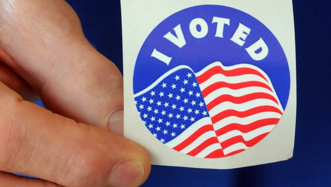 A North Carolina voter shows off his sticker during the early voting process in 2012.