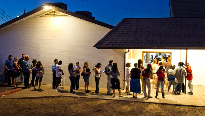 About 100 people wait in line (it goes around the corner) to vote at the First New Life Missionary Baptist Church at 19th Avenue and Roeser in Phoenix in 2012.
