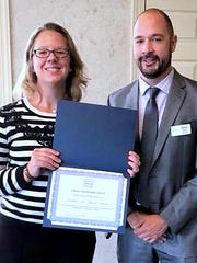 Mandy Fleming, technical services manager at the Southern Tier Library System, and system Executive Director Brian Hildreth show off an award the library system recently attained.