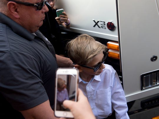 Mason Ramsey exits his tour bus to perform at the Walmart