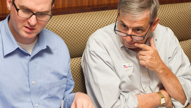 Livingston County Prosecutor William Vailliencourt, right, studies the tally of votes in his race against Carolyn Henry. Vaillencourt, seated with Mike Taylor, and surrounded by a group of supporters at Bar None Steak & Fish, came out on top in the primary and will run unchallenged in the November general election.