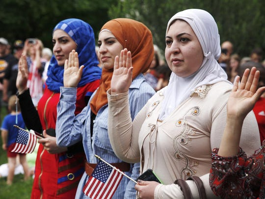 From left, Duaa Abdullah, Shams Abdullah and Alaa Abdullah raise their hands as they take the Oath of Allegiance to become naturalized American citizens in a ceremony Saturday at the Genesee Country Village & Museum. The women are all from Iraq.