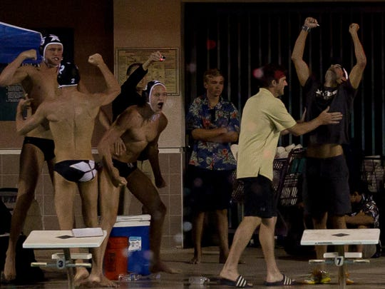 Xavier Prep's coach Pavol Valovic (right) and his players react as Xavier Prep wins the DVL championship water polo game against Palm Desert.