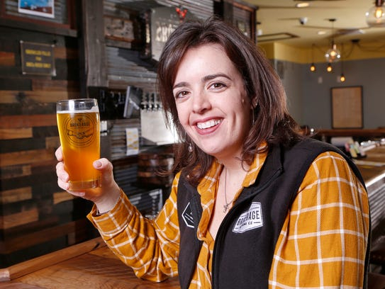Co-owner Stacy Grove hoists a pint of Nola's Golden