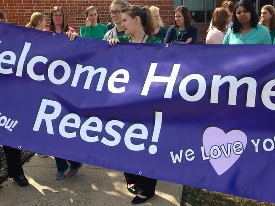 Teachers unfurl a banner they designed  Thursday, March 17, 2016 in front of Mercersburg Elementary School to celebrate the return of student Reese Burdette. Reese was severely injured in a fire and has spent the last two years at Johns Hopkins Medical Center in Baltimore.