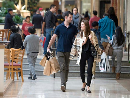 FILE - In this Friday, Nov. 25, 2016, file photo, Eric Denker and his wife, Jalen Denker, of Irvine, take advantage of sales to buy suits for business school interviews at South Coast Plaza in Costa Mesa, Calif. On Friday, Dec. 2, 2016, the U.S. government issues the November jobs report.