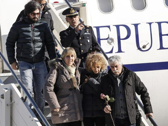 Gaetano Di Agostino, bottom right, father of Italian victim Fabrizia Di Lorenzo, holds a rose as he is followed by his wife Giovanna, center, and his son Gerardo, top left,, while disembarking a plane carrying the coffin of their daughter from Berlin at Rome's military airport of Ciampino, Saturday, Dec. 24, 2016. Di Lorenzo, 31, is among the 12 people who perished when a truck plowed through a Christmas market in Berlin last Monday.