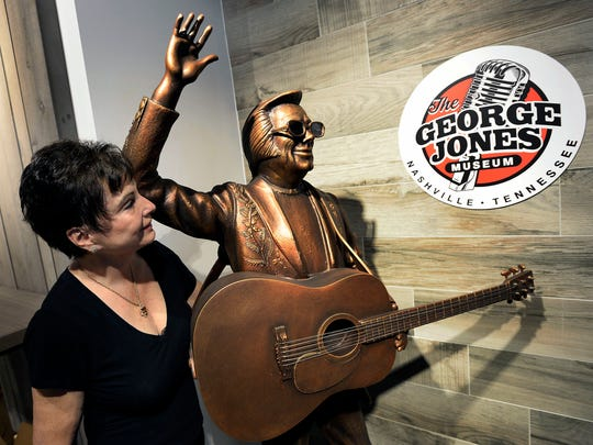 Nancy Jones admires a statue of her late husband, George