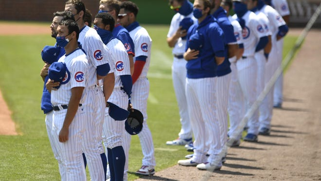 Members of the Chicago Cubs during the national anthem before a baseball game against the Milwaukee Brewers Saturday, July 25, 2020, in Chicago. Milwaukee won 8-3.