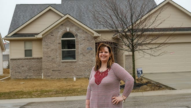 Lorraine Pitkin of Burton stands outside her newly built detached condo in the Mallard Ponds Condominiums subdivision in Burton on Tuesday, April 3, 2018.