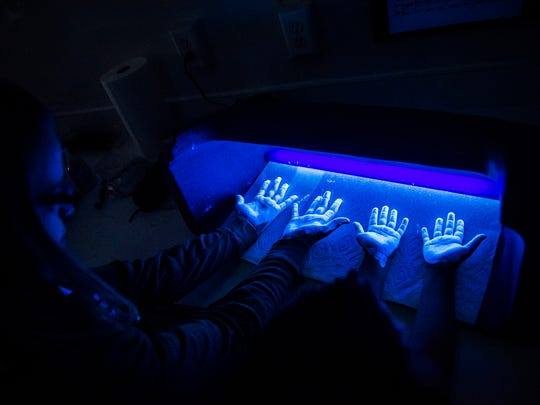 Third grade students at West Manheim Elementary school place their hands under a UV light to visibly identify germs and bacteria on their hands with a fluorescent lotion Tuesday inside the mobile AgLab that was visiting the school.