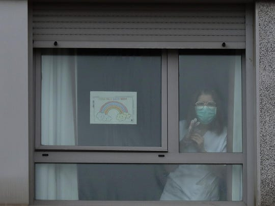 "A nurse looks out from a window next to a banner reading in Spanish ""Everything is going to be all right"" inside of a nursing homes where dead bodies were found at the nursing homes of Usera in Madrid, Spain, Tuesday, March 24, 2020. Spanish army troops disinfecting nursing homes have found, to their horror, some residents living in squalor among the infectious bodies of people that authorities suspect have died from the new coronavirus. Prosecutors have launched a judicial probe. For some, it can cause more severe illness, especially in older adults and people with existing health problems. (AP Photo/Manu Fernandez)"