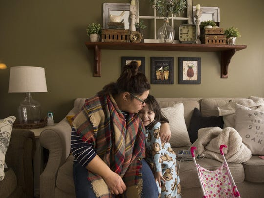 Liz Theisen gives a kiss to her daughter Emily, at their home in Noblesville, Tuesday, January 24, 2017. On Tuesday, January 31, Emily will undergo a 14-18 hour surgery at the Cincinnati Children's Hospital that will reroute or remove several of her internal organs, and will remove her pancreas as well as the chronic pancreatitis that plagues the four-year-old.