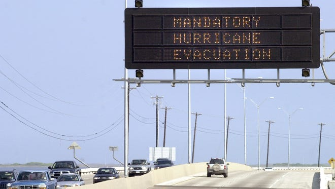 A lone vehicle makes its way out onto the John F. Kennedy Causeway on its way to Padre Island Wednesday, Sept. 21, 2005 after passing under a Mandatory Hurricane Evacuation highway sign for the island and Flour Bluff neighborhood.