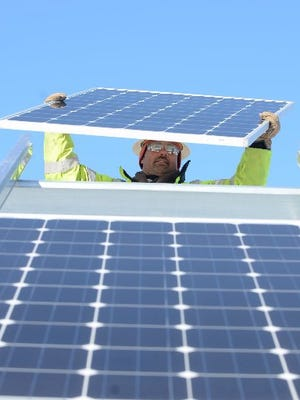 Electrician Bill Dillionson guides a solar panel in place at the DTE solar farm in Lyon Township on March 3, 2014.