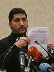 Osama Abu Zeid of the the main moderate Syrian opposition group Free Syrian Army, shows what he said is a copy of the five-point cease-fire agreement for Syria, during a news conference in Ankara, Turkey, Thursday, Dec. 29, 2016. Abu Zeid said that his group, one of the 13 armed opposition factions, had agreed to abide by the nationwide cease-fire agreement that will go into effect at midnight Thursday. The truce will be followed by peace talks in Kazakhstan that will focus on finding a solution for Syria's crisis, Abu Zeid said.