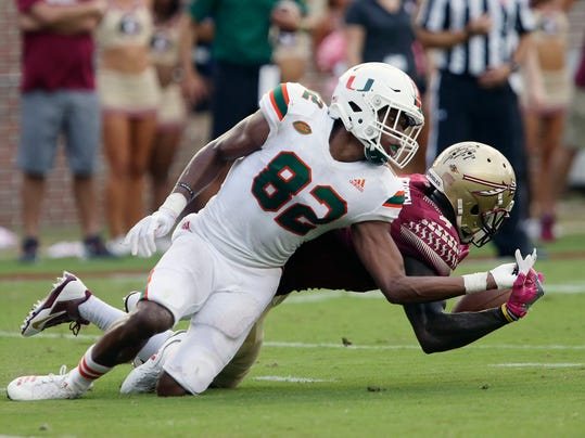 Miami receiver Ahmmon Richards and Florida State defender Tarvarus McFadden try to catch a low pass in the third quarter of an NCAA college football game, Saturday, Oct. 7, 2017, in Tallahassee, Fla. Miami won 24-20. (AP Photo/Steve Cannon)