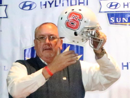 Bill Coon, board president of the Sun Bowl Association holds up a North Carolina State Helmet Sunday at Sunland Park Racetrack and Casino.