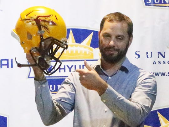 Ben Leeser of Hyundai of El Paso holds up an Arizona State helmet Sunday at Sunland Park Racetrack and Casino.