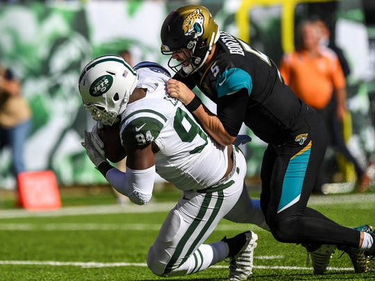 Oct 1, 2017; East Rutherford, NJ, USA;New York Jets outside linebacker Kony Ealy (94) is tackled by Jacksonville Jaguars quarterback Blake Bortles (5) after an interception during the 3rd quarter at MetLife Stadium. Mandatory Credit: Dennis Schneidler-USA TODAY Sports