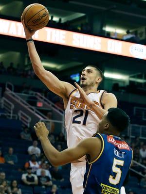 Oct 13, 2017; Phoenix, AZ, USA; Phoenix Suns center Alex Len (21) drives past Brisbane Bullets guard Stephen Holt (5) in the first half at Talking Stick Resort Arena. Mandatory Credit: Rick Scuteri-USA TODAY Sports