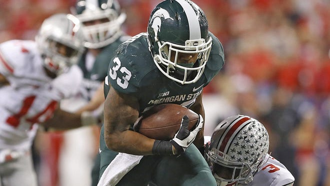 Michigan State running back Jeremy Langford scores a touchdown with a little more than 2 minutes left as Ohio State's Bradley Roby (1) and Corey Brown (3) can't make the stop in the Big Ten championship game at Lucas Oil Stadium on Dec. 7, 2013. Michigan State won, 34-24.