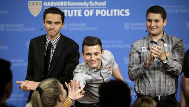 In this March 20, 2018, file photo, Marjory Stoneman Douglas High School student Cameron Kasky, center, reaches out to clasp hands with Jaclyn Corin, below left, while David Hogg, top left, and Alex Wind, right, applaud at the conclusion of a panel discussion about guns at the Harvard Kennedy School Institute of Politics in Cambridge, Mass.